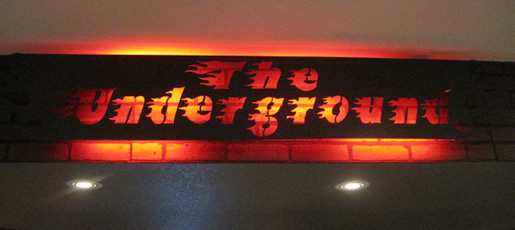The underground bar in a private residence has this custom lit up cnc metal designed sign.